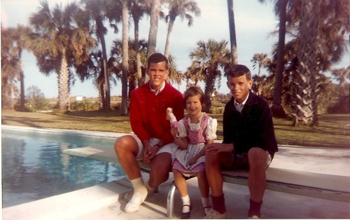 """Christmas 1964 with my brothers. The lagoon is in the background. I'm showing off a brand new """"Skipper"""" doll (Barbie's younger sister) and wearing some sort of Swiss costume that a relative had sent me from a trip to Europe."""